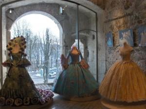 Razkošne obleke v razstavnem prostoru peterokotnega stolpa. V ozadju je viden veliki in mali vhod, ki je bil nekoč glavni vhod na Ljubljanski grad