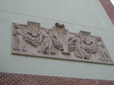 Relief prikazuje dekleta, ki med girlandami držijo grbe Kranjske, Ljubljane in Josipa Gorupa Slavinjskega.
