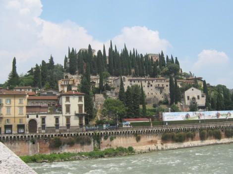 Grad ob Adiži. Ob reki je bilo nekoč gledališče, predstave ob različnih priložnostih, uprizarjajo še danes.