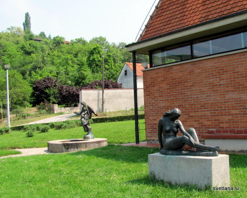 Kip dekleta, v ozadju vodnjak in kip mame z otrokom.