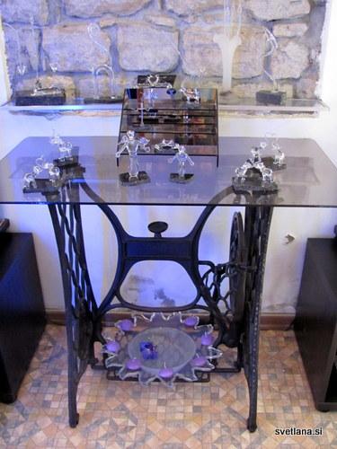 Stojalo starega šivalnega stroja Singer je odličen razstavni prostor za izdelke iz stekla